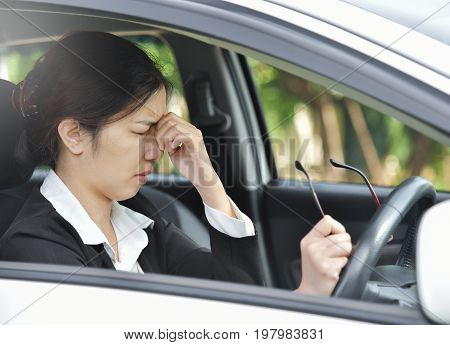 Asian glasses business woman having headache from migraine while driving a car. Illness exhausted disease tired for overtime working concept.