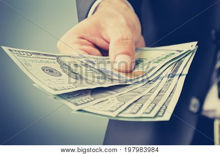 Businessman hand giving money US dollars (USD) - vintage style color effect