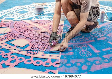 Tools of the street artist and colored pattern on a street of abstract city