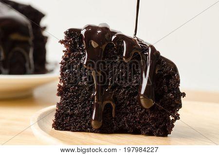 Pouring chocolate sauce on piece of chocolate cake
