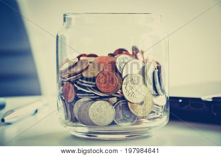 Coins in the glass jar mixed Asian multi currencies - vintage (retro) color effect