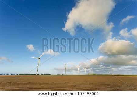 Wind Turbines For Electricity Generation In Agricultural Field On A Cloudy Day In Normandy, France.