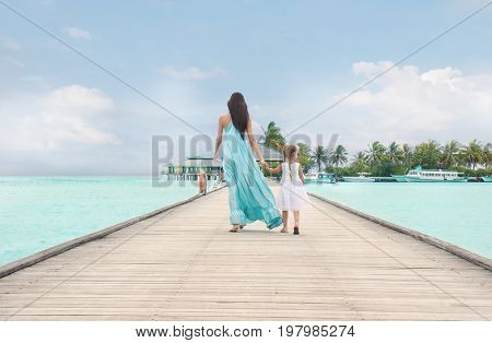 Beautiful young woman with her daughter at sea resort