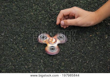 Child playing with popular gadget. Modern toy spinner in movement.