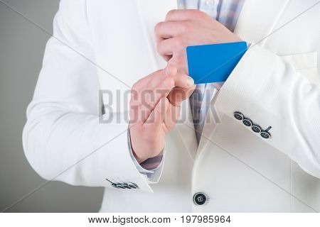 Businessman in white jacket on grey background. Empty business card in cuff. Ace up sleeve concept. Advantage and secret trump. Cheating and trick