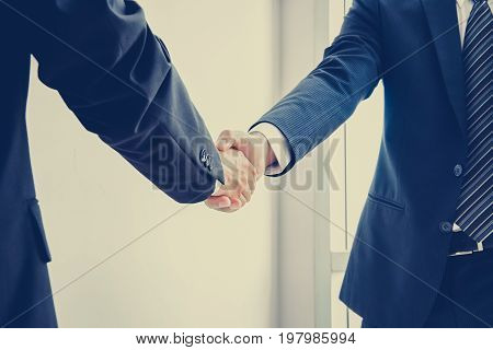 Handshake of businessmen; success dealing & business partner concepts - vintage color effect with soft focus