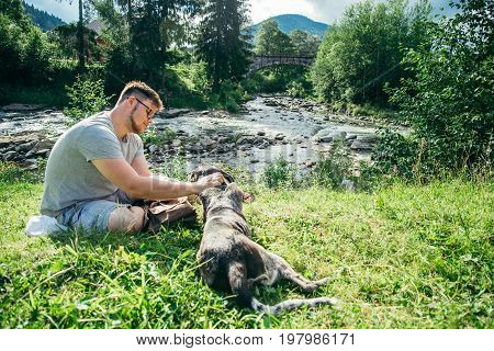 young strong man with backpack stays near mountains river with dog and looking for the view