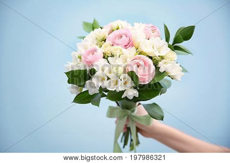 Female hand holding beautiful bouquet with white freesia on light background