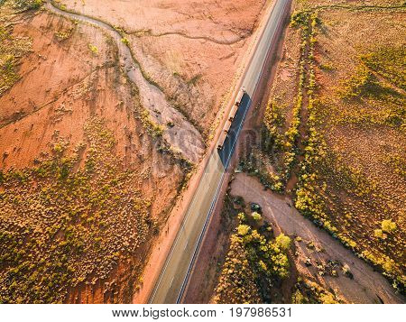 Aerial photograph of Australian outback and dry road with roadtrain surrounded by gum trees and Spinifex.