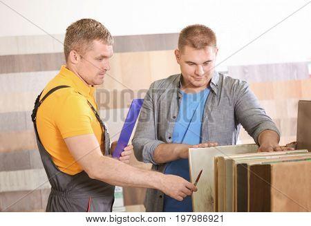 Carpenter taking order from customer in hardware store
