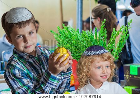 The Jewish holiday of Sukkot,  Holiday market in Jerusalem. Cute little boy with long blond hair in  knitted skullcap and  seven year old boy in white skullcap with etrog.