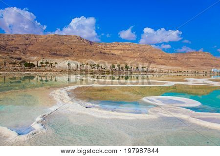 The concept of ecological and medical tourism. Reduced water in the salty Dead Sea, Israel. The evaporated salt has developed into very fantastic patterns