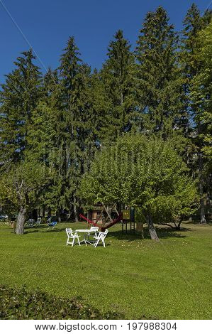 Autumnal view toward public garden with picnic table at chair lawn, tree and open-air kindergarten, Cortina d'Ampezzo, Dolomites, Alps, Veneto, Italy, Europe