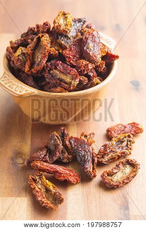 Dried sliced tomatoes in bowl on wooden table. Tomatoes as superfood.