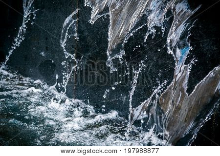 Background with running water. An element of a street fountain. Water running down the wall. Abstract background and water wallpaper