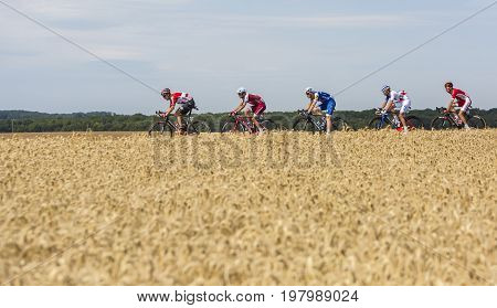 Vendeuvre-sur-Barse France - 6 July 2017: A group of five cyclists in front of the peloton pass through a region of wheat fields during the stage 6 of Tour de France 2017.