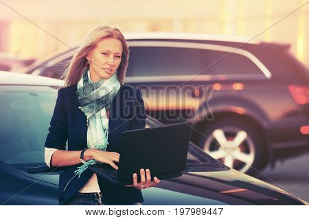 Young fashion business woman with laptop next to her car on parking. Stylish female model in black jacket and blue scarf outdoor