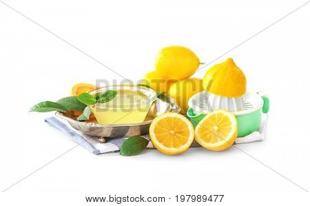 Composition with squeezer, lemons and juice on white background