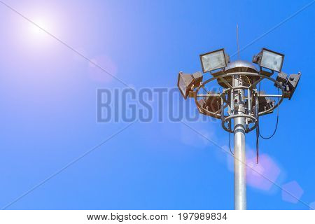 Large tall high outdoor stadium halogen spotlight with lamp light turned off and blue sky with sunshine.