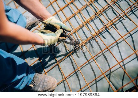 Worker Using Pincers And Steel Wire To Secure Bars For Concrete Pouring On Industrial Construction S