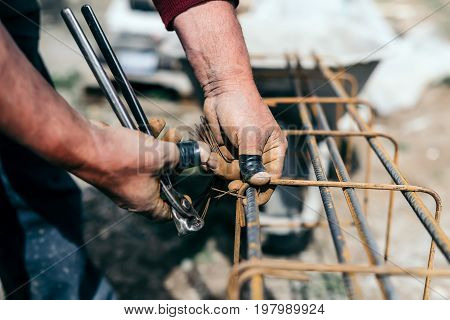 Worker Hands Using Steel Wire And Pincers To Secure Steel Bars, Preparing For Concrete Pouring On In
