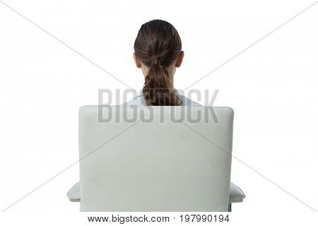 Rear view of female executive relaxing on chair against white background