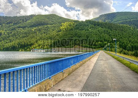 Road over dam of hydroelectric power station. Mountain landscape with a dam