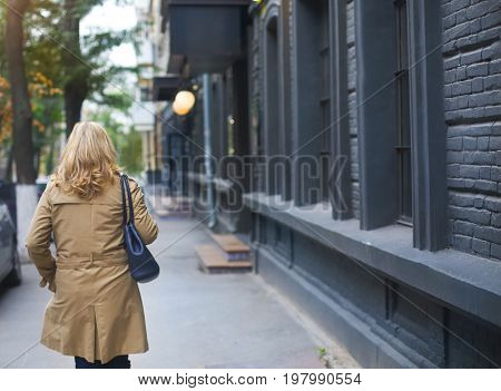 Middle age women goes through the city and smiles. Loneliness concept.