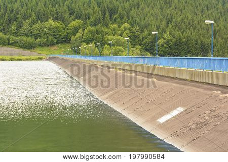 Hydroelectric power dam lined with blue railings and lamps. Mountain Reservoir