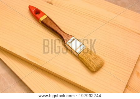 Close up joiner's brush tool lying on qhite wooden plank