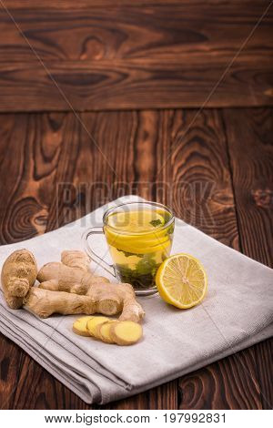 A top view of a glass cup full of green tea on a wooden background. A cup of hot beverage, ginger root and sour lemon slices on a fabric table cloth. Winter organic beverage. Healthy tea. Copy space.