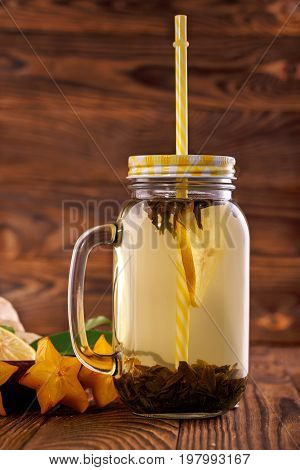 Close-up of a jar with a yellow straw filled with bright natural hot beverage on a wooden background. A tasty and healthy drink next to carambola, mint,  and cut lemon in a mason jar. Copy space.