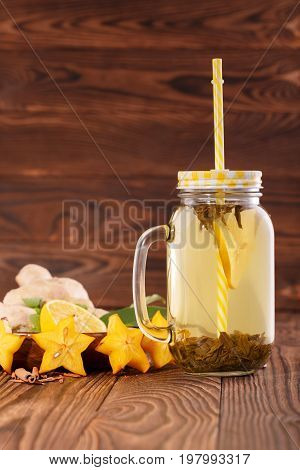 A glass jar with a bright straw full of yellow natural hot beverage on a wooden background. A tasty and healthy drink next to ginger, carambola, mint, cinnamon and cut lemon in a mason jar. Copy space