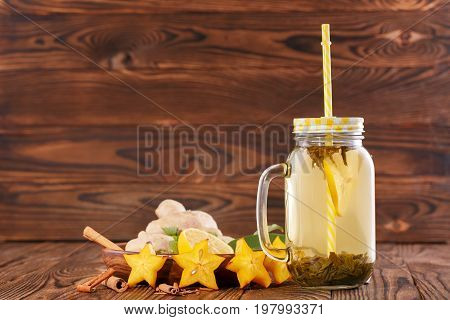 A close-up of a glass jar with a yellow straw full of organic healthy beverage on a wooden background. A tasty and healthy drink next to ginger, carambola, cinnamon and cut lemon. Copy space.