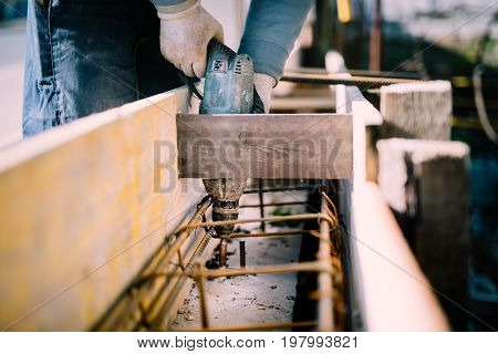 Worker Using A Drilling Power Tool On Construction Site And Creating Holes In Cement For Foundation