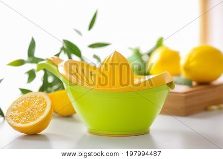 Plastic squeezer and half of lemon on light table
