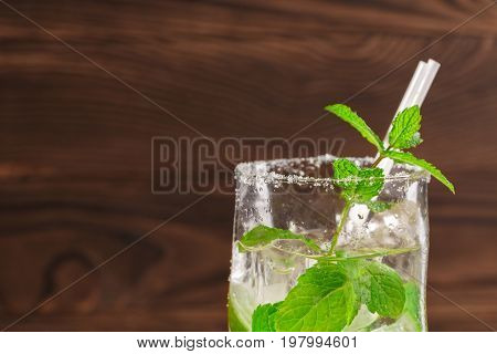 Close-up of a highball glass full of refreshing mojito drink with rum, fresh lime, bright mint twigs, crushed ice and little white straws on a dark wooden background. Copy space.