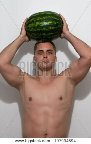 The guy is holding a huge watermelon on his head. A guy with a bare torso on a light background.
