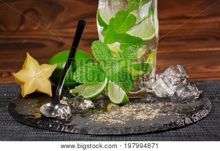 Close-up of summer mojito drink with rum, lime, mint, carambola, ice and brown sugar on a dark background. A glass full of alcohol drink from lime, rum, mint and ice cubes. Cold drinks.