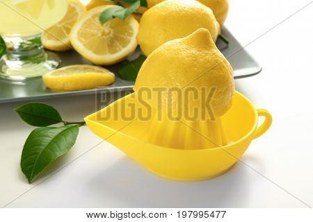 Yellow squeezer with half of fresh lemon on white background