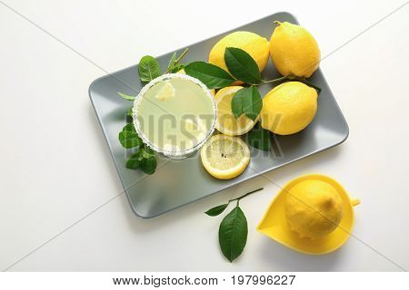 Platter with glass of juice, lemons and squeezer on white background