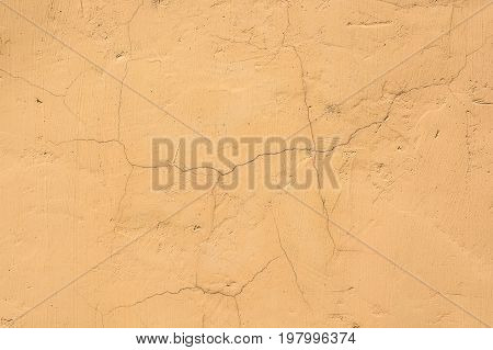 Abstract texture of wall covered with obsolete orange cracked cement plaster