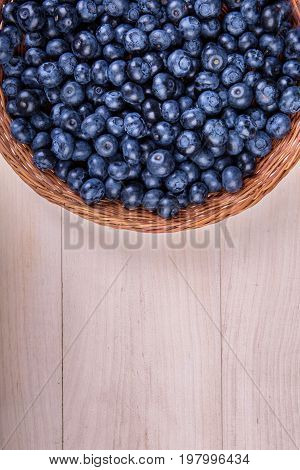 Top view of bright juicy blueberries in a wooden basket. Fresh dark blue berries on a light wooden background. Ripe fruits and berries in a brown crate. Natural summer berries for dessert. Copy space.