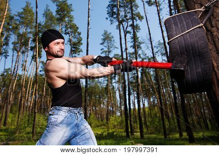 Strong Healthy Adult Ripped Man With Big Muscles Hitting Car Tyr
