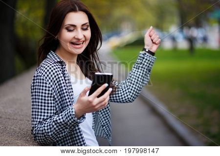 Young Pretty Stylish Exulting Woman Holding Smart Phone In The S