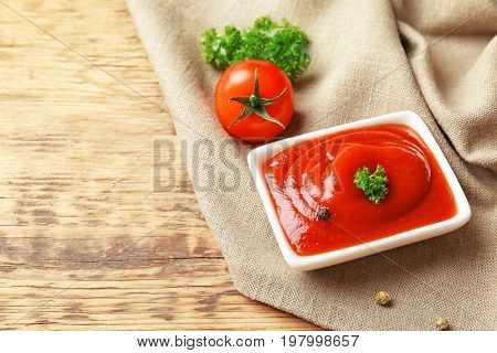 Bowl with sauce, tomato and spices on wooden table