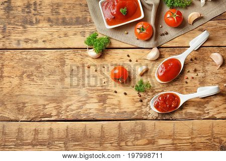 Ceramic spoons with tomato sauce and spices on wooden table