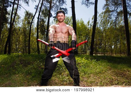 Lumberjack Worker Standing With Two Big Crossed Axes In The Fore