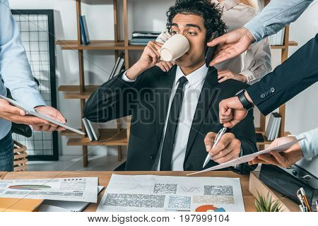 Portrait Of Busy Businessman Drinking Coffee And Sitting At Workplace While Colleagues Helping With