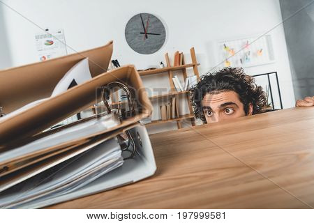 Obscured View Of Businessman Hiding Behind Table And Looking At Folders While Missing Deadline